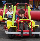 Two children driving karts at an outdoor event